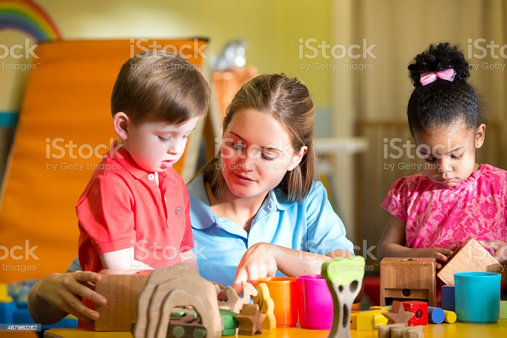 Nursery teacher supervising children playing with building blocks stock photo