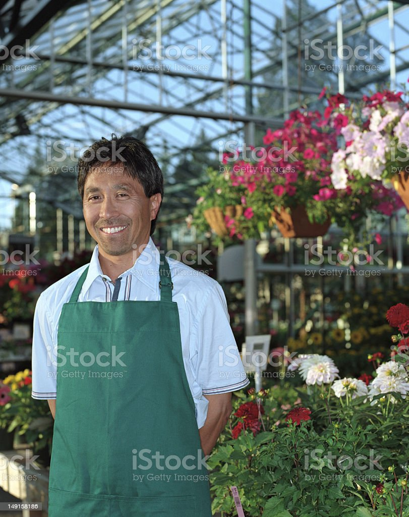 Nursery worker surrounded by plants in greenhouse, portrait royalty-free stock photo
