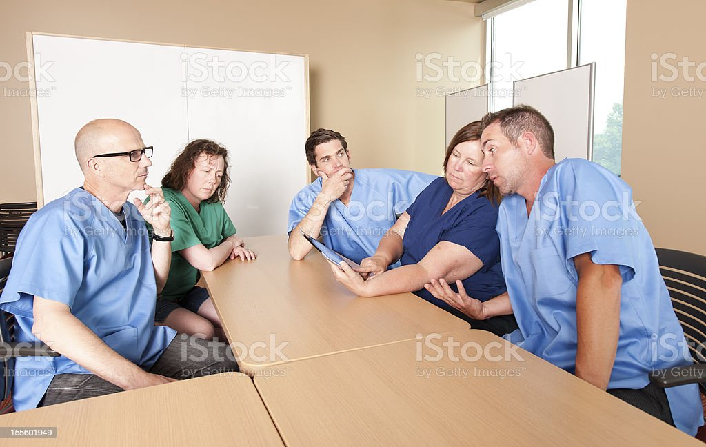 Nurses Meeting around a table in a hospital. stock photo