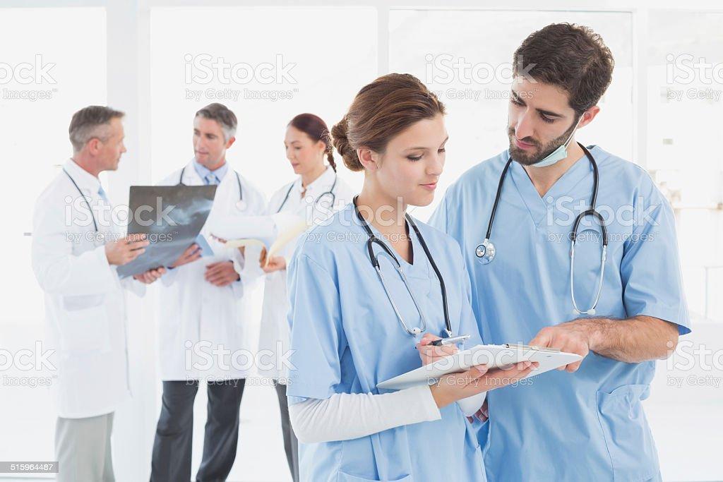 Nurses reading a file together stock photo