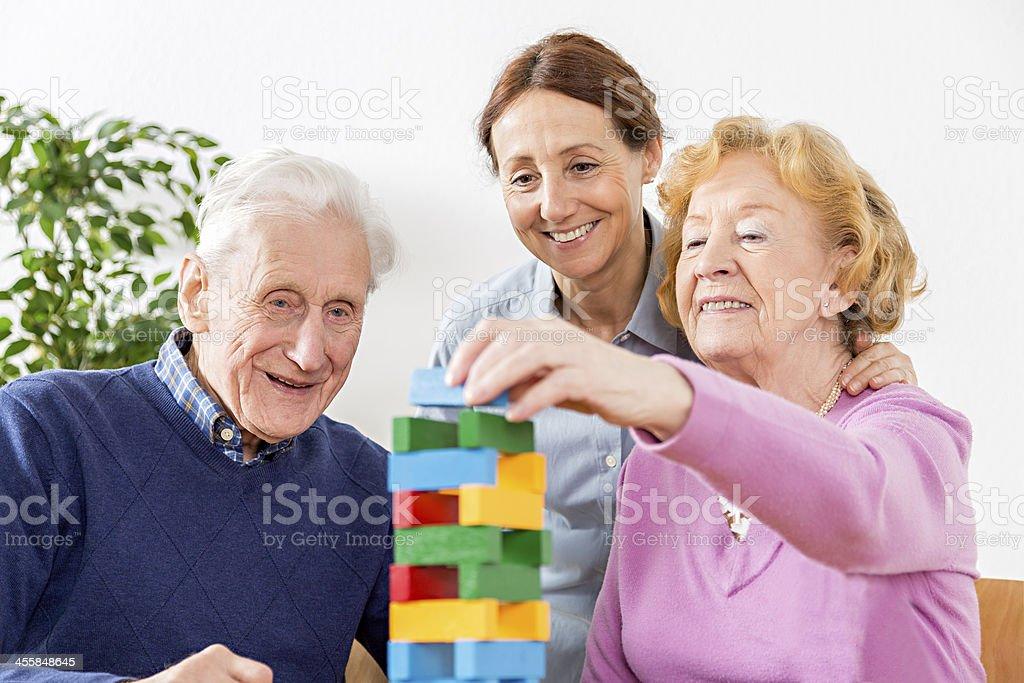 Nursing Home – senior couple playing with wooden blocks stock photo