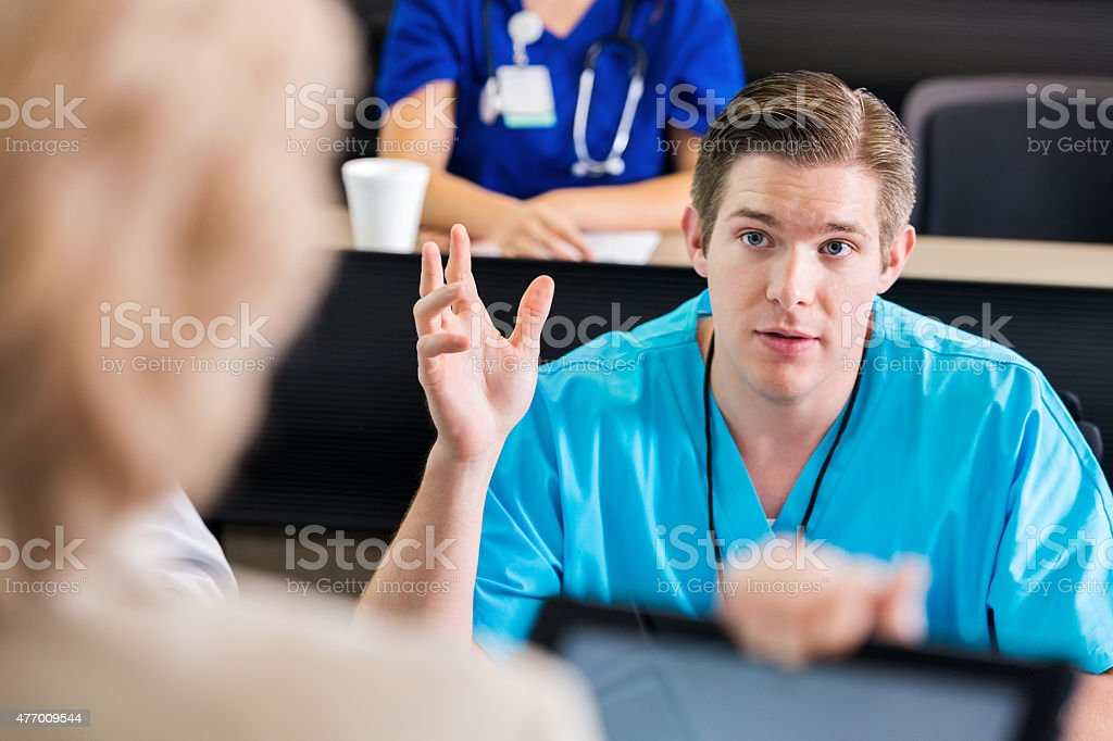 Nursing or medical student asking question during healthcare conference seminar stock photo