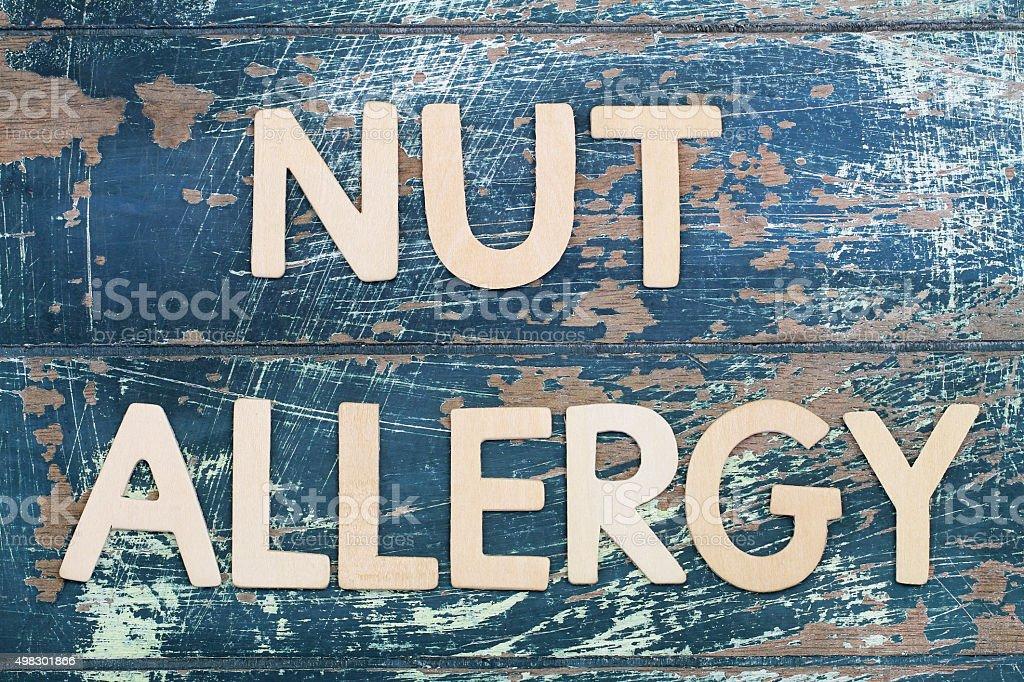 Nut allergy written on rustic wooden surface stock photo