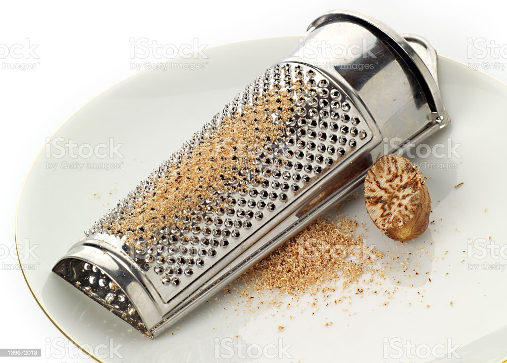 Nutmeg and grater on a plate, with freshly ground spice royalty-free stock photo