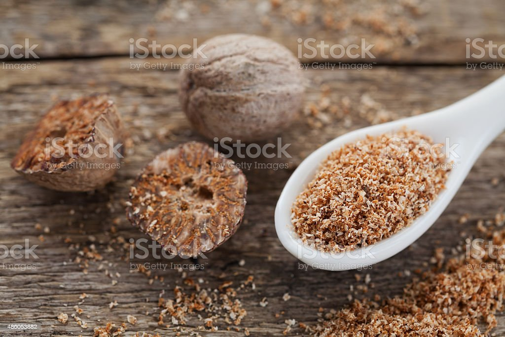 Nutmeg whole and grated on wooden background stock photo