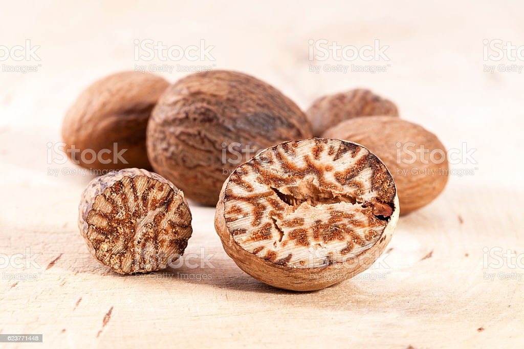 Nutmeg , whole and half on wooden plank, close up stock photo