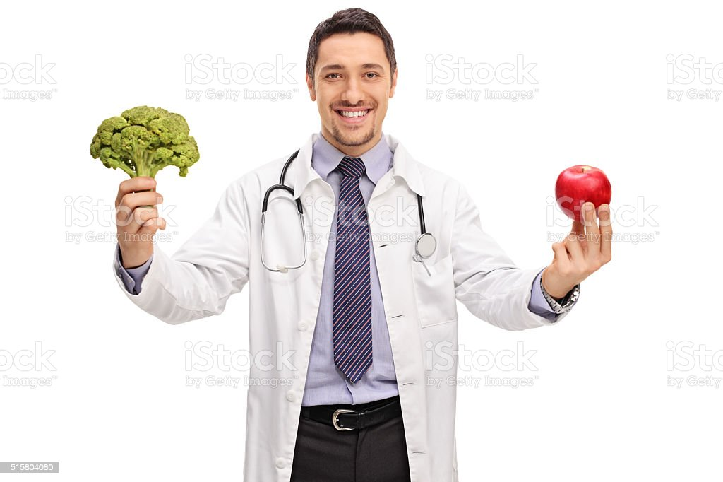 Nutritionist holding a broccoli and an apple stock photo