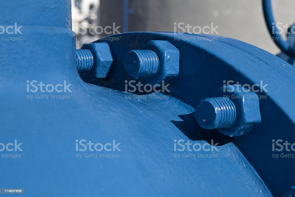 Nuts and Bolts on Huge Blue Pipe royalty-free stock photo