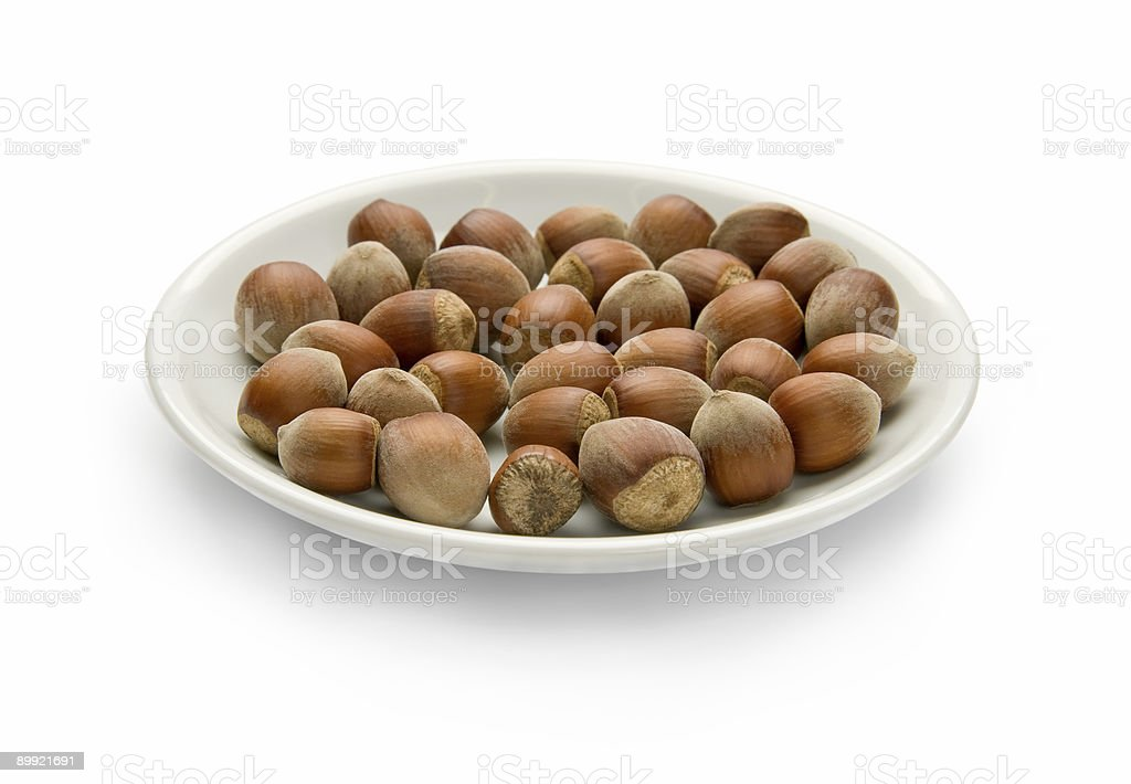 Nuts in a plate, isolated on white background royalty-free stock photo