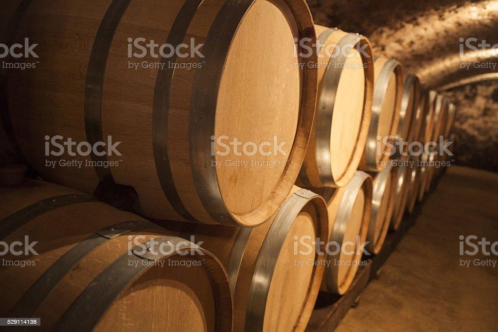 Oak Barrels in a Cellar for Aging Red Wine stock photo