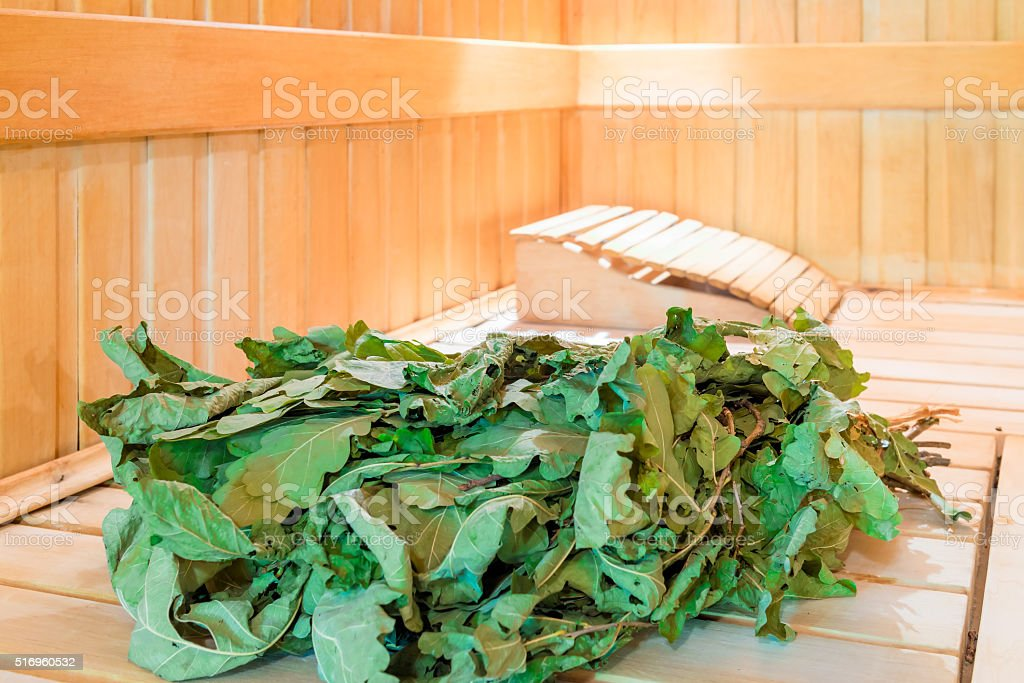 Oak bath broom lying in a sauna stock photo