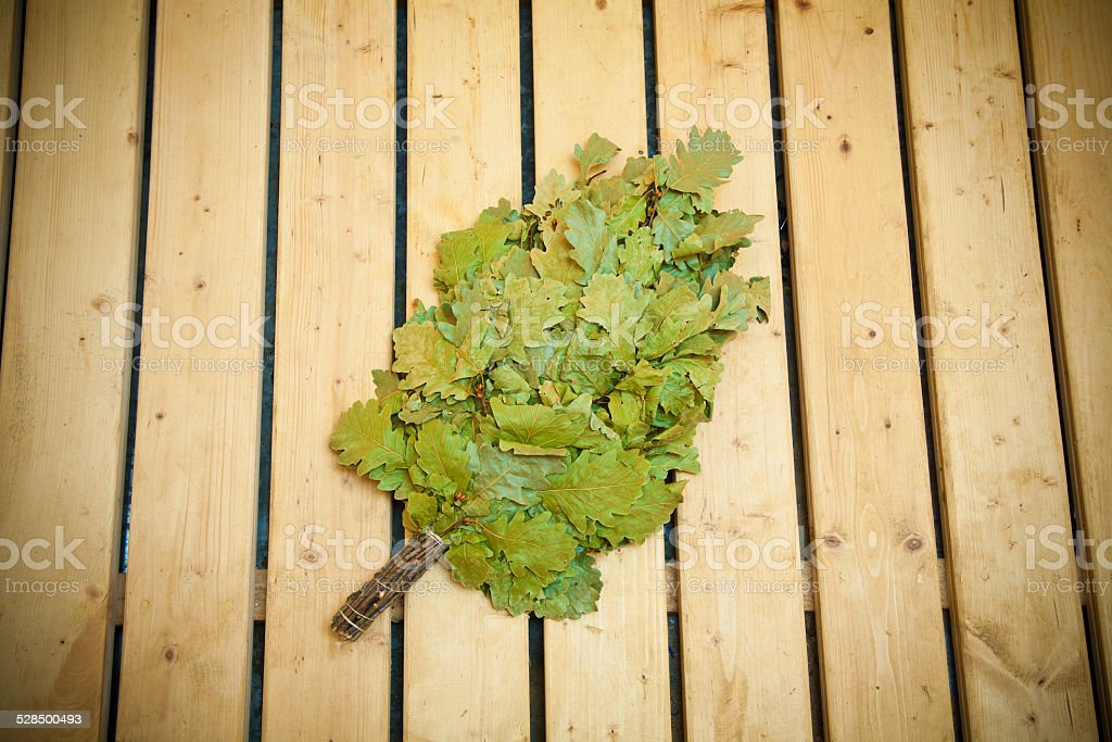 Oak broom on wooden boards for baths and saunas stock photo