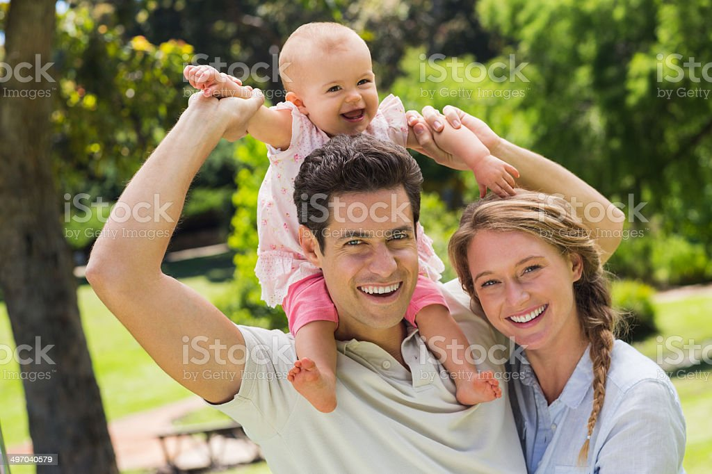 Oarents with their cheerful little baby at park royalty-free stock photo