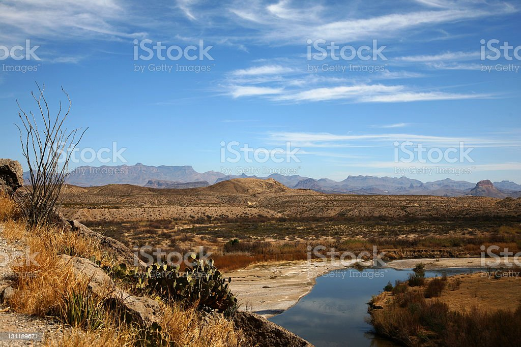 Oasis at the edge of a desert with mountain range from afar stock photo