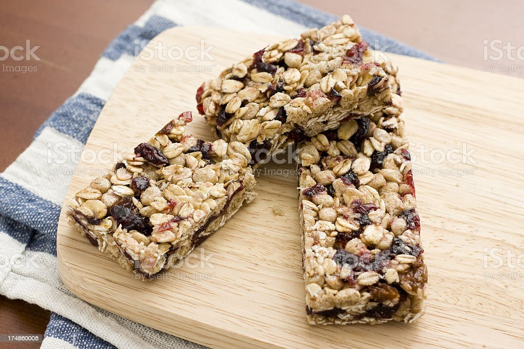 Oat and red berry granola bars on a wooden board royalty-free stock photo