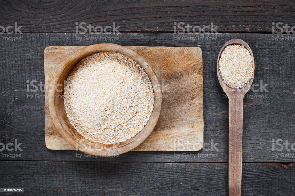 Oat bran in the wooden bowl stock photo