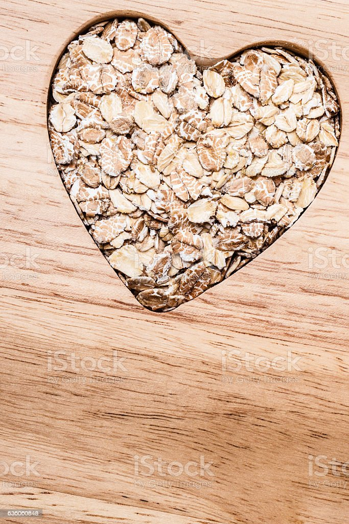 Oat cereal heart shaped on wooden surface. stock photo