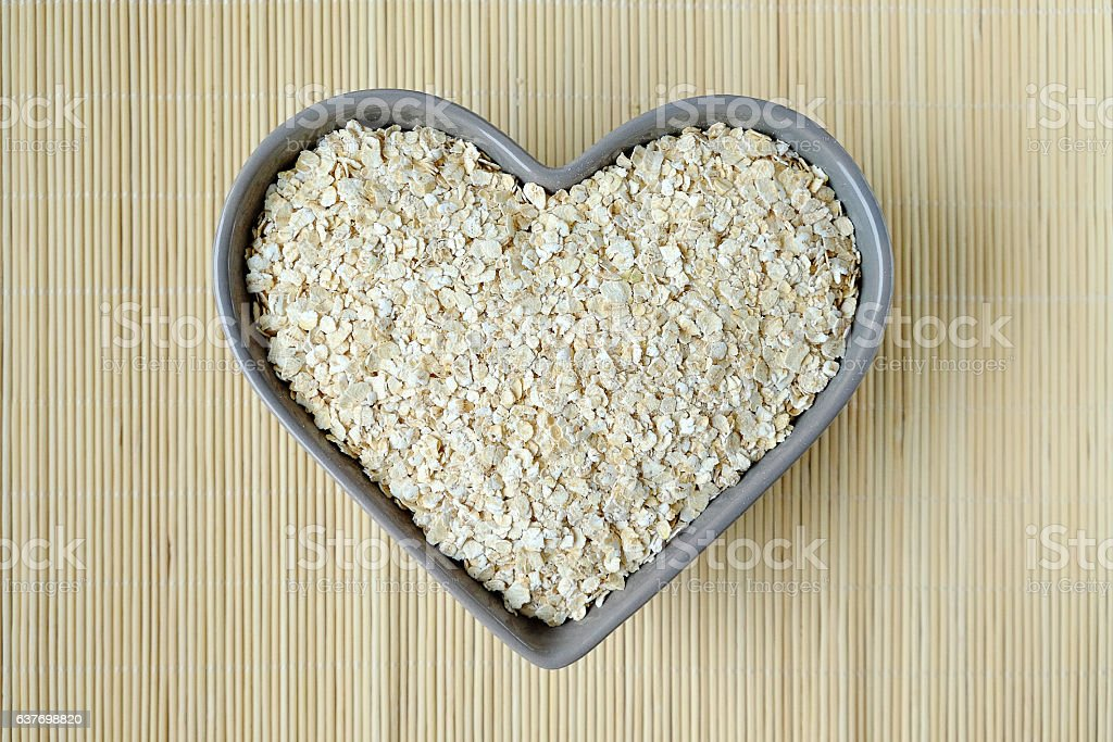 Oat flakes in a bowl in the shape of heart. stock photo