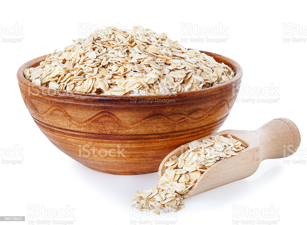 Oat flakes in bowl and wooden spoon on white background stock photo