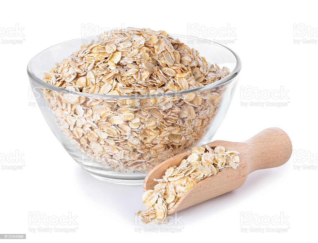 Oat flakes in glass bowl and wooden spoon on white stock photo