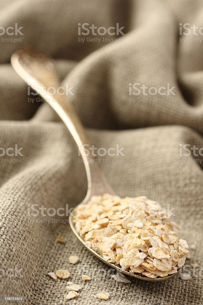 Oat flakes in metal spoon on sackcloth background royalty-free stock photo