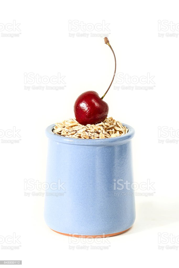 oat flakes with cherries in a ceramic jar stock photo