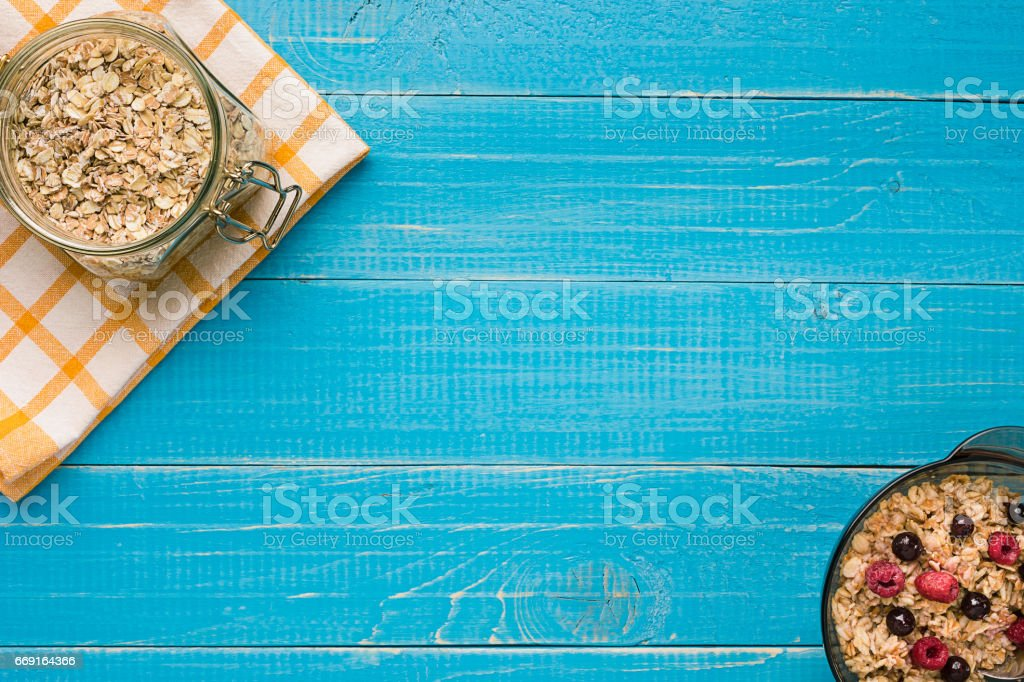 oat flakes with milk and berries bowl with spoon on blue wooden background, top view stock photo
