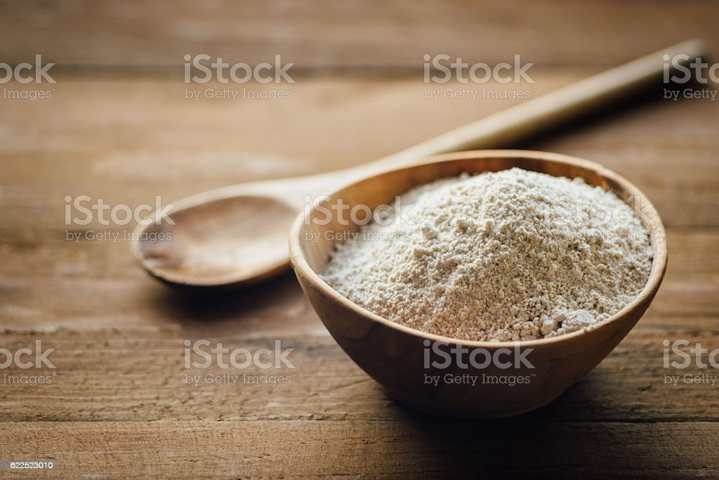 Oat flour in old wooden bowl stock photo