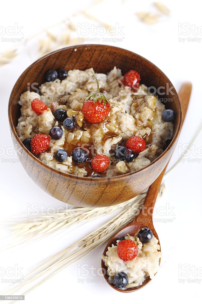 oat porridge with fresh berries on a white background royalty-free stock photo