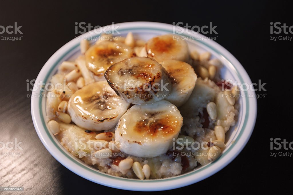 Oat porridge with pine nuts and torched bananas stock photo