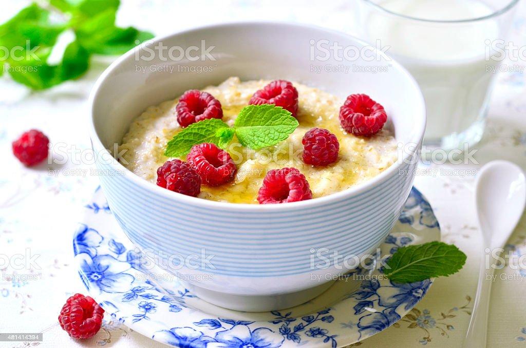 Oat porridge with raspberry and honey. stock photo