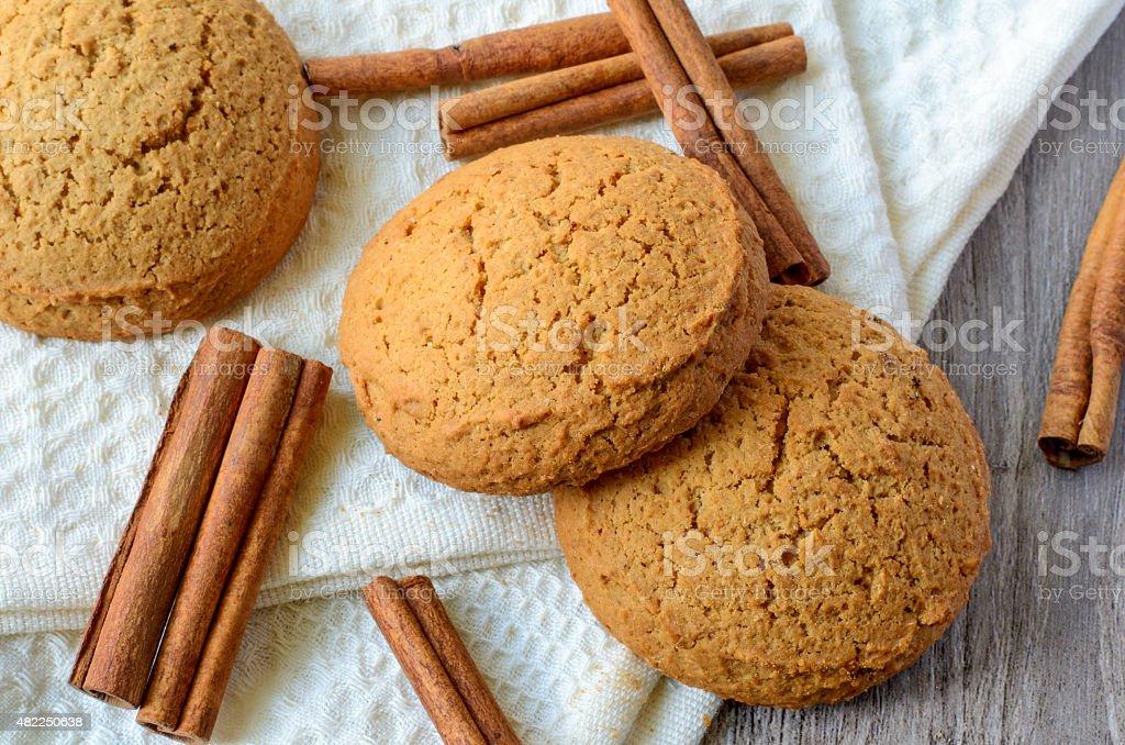 Oatmeal cookies and cinnamon sticks stock photo