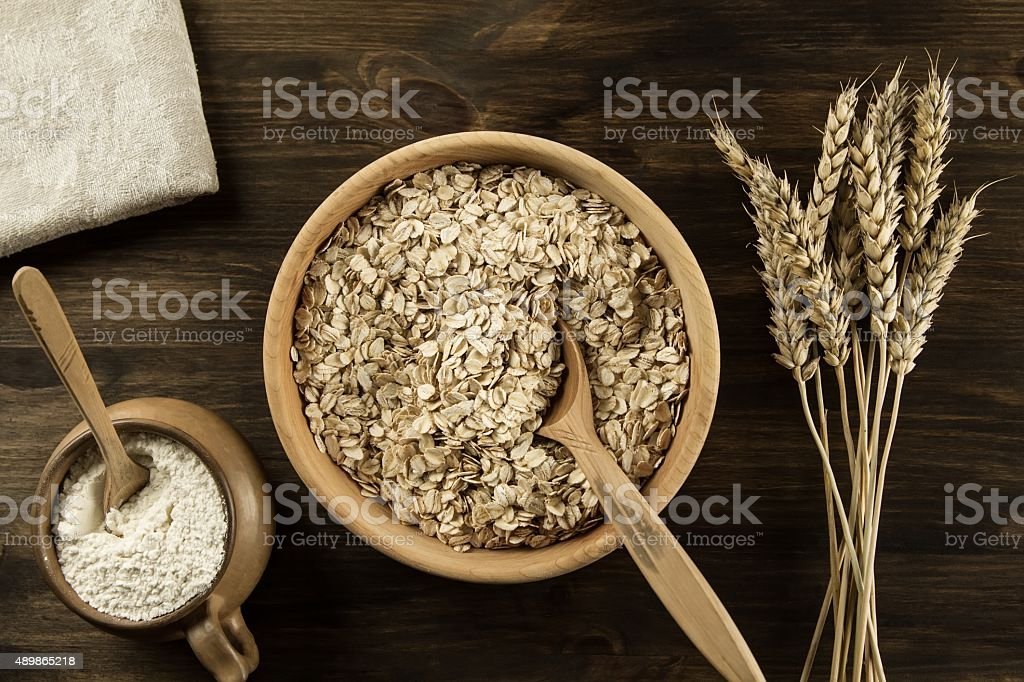 oatmeal flakes in a wooden bowl stock photo