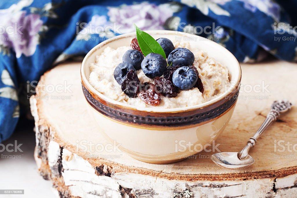 Oatmeal porridge berries, blueberries, raisins, birch, cut stock photo