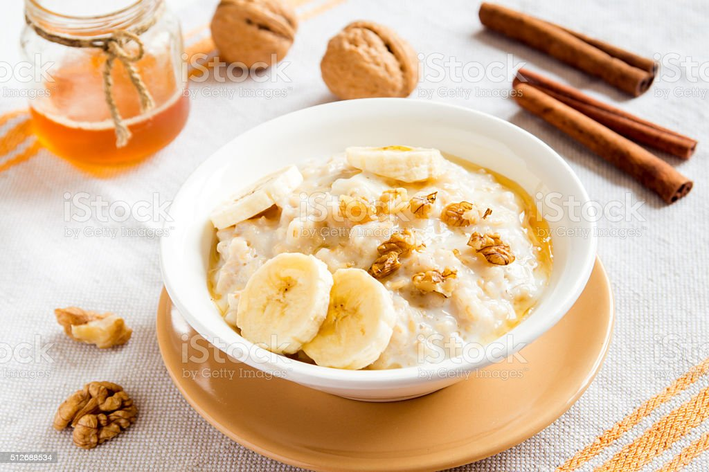 oatmeal porridge with banana, nuts and honey stock photo