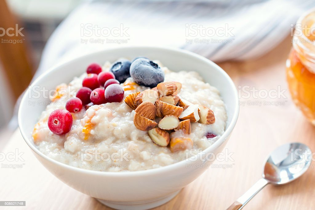 Oatmeal porridge with berries and nuts in bowl stock photo