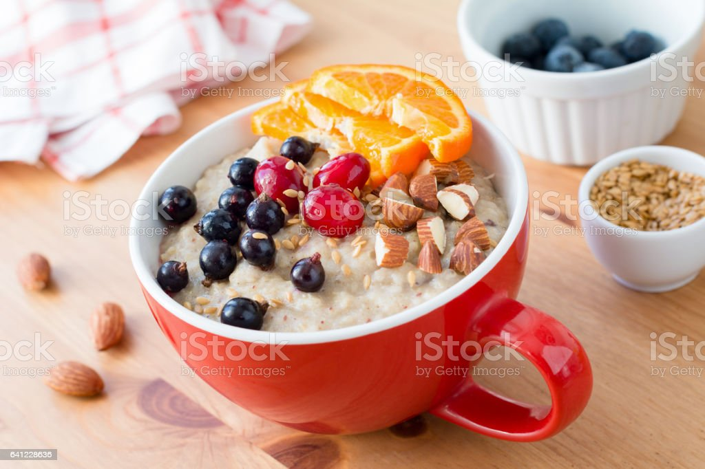 Oatmeal porridge with berries and nuts stock photo