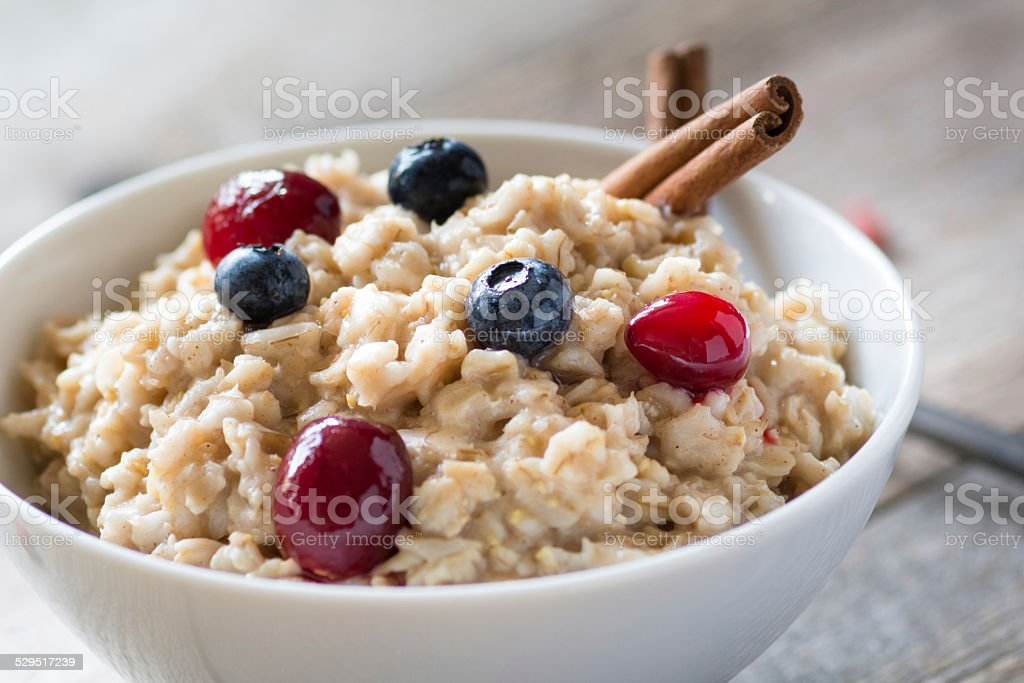 Oatmeal porridge with blueberries and cranberries stock photo
