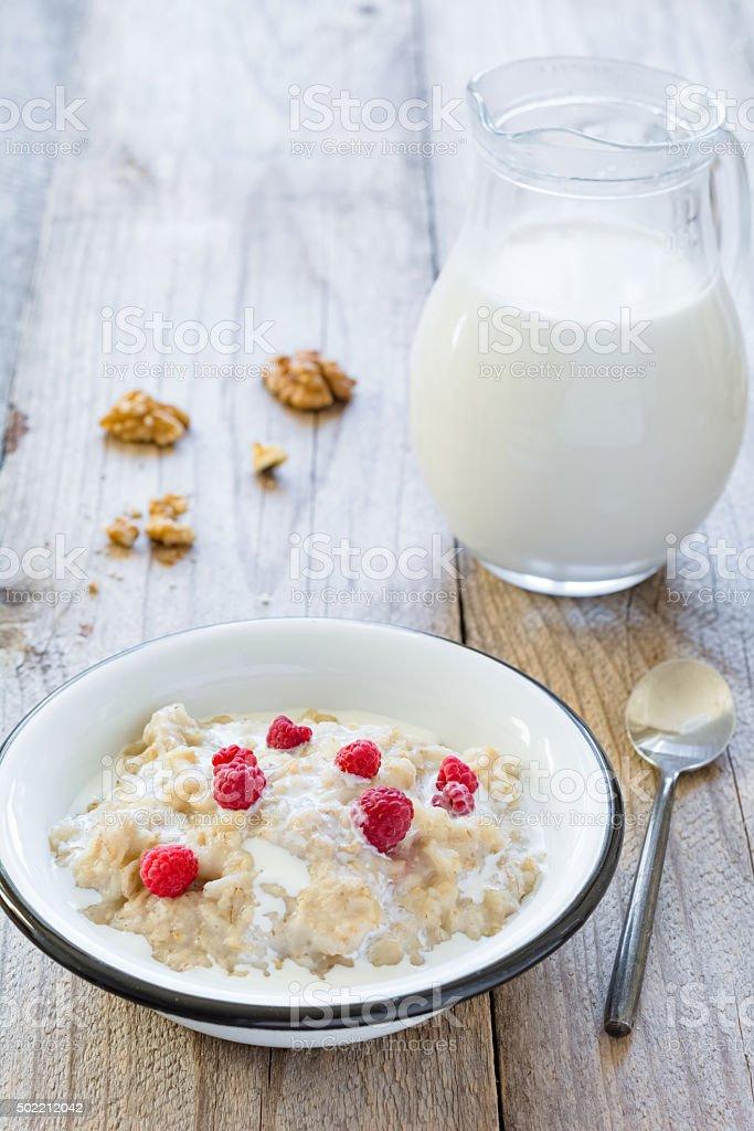 Oatmeal porridge with raspberries and milk stock photo