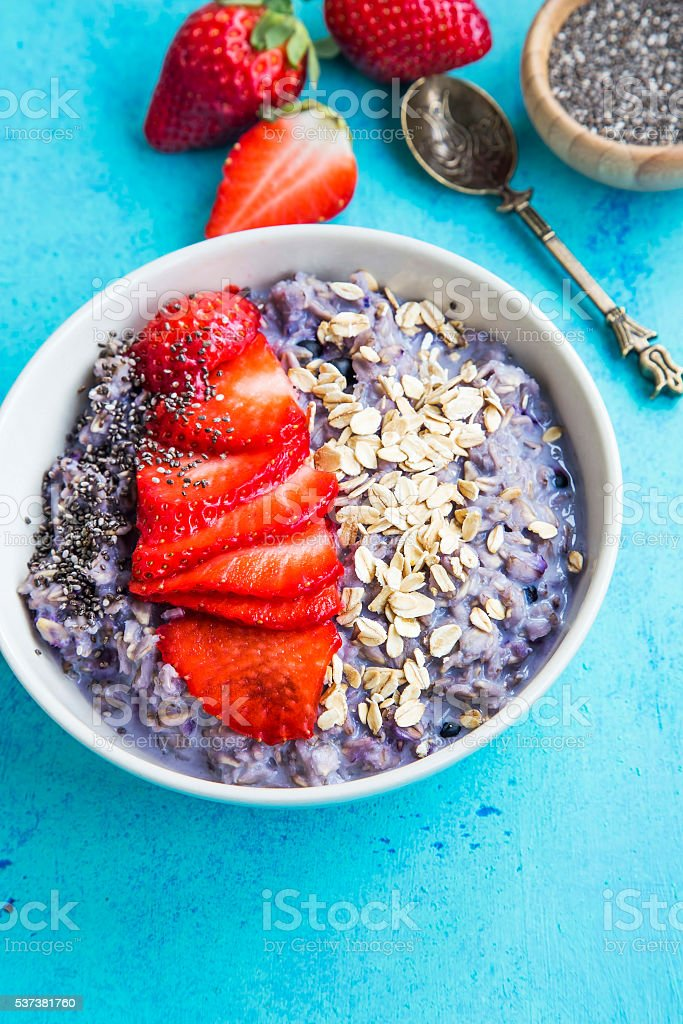 Oatmeal porridge with strawberry slices and chia seeds stock photo