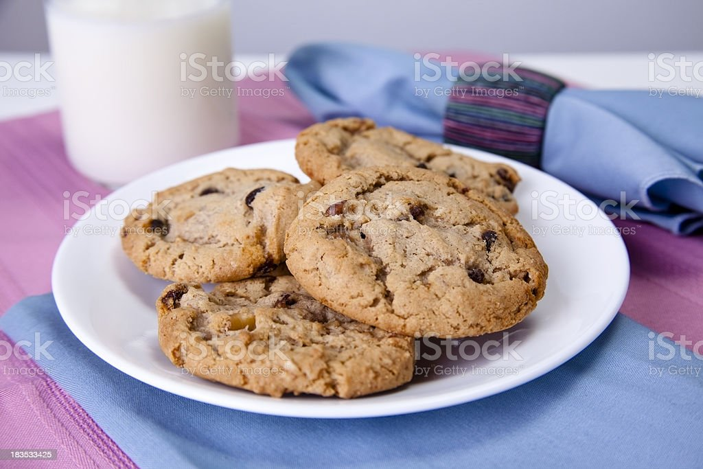 Oatmeal raisin cookies on plate with glass of milk. stock photo