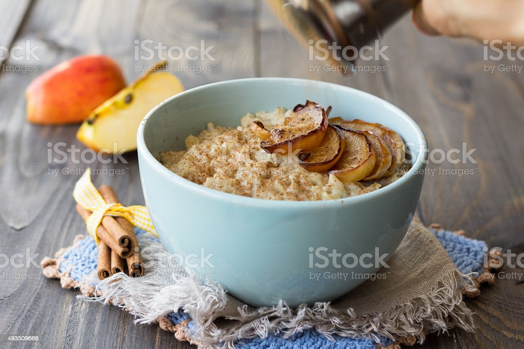 Oatmeal with baked apples and cinnamon stock photo
