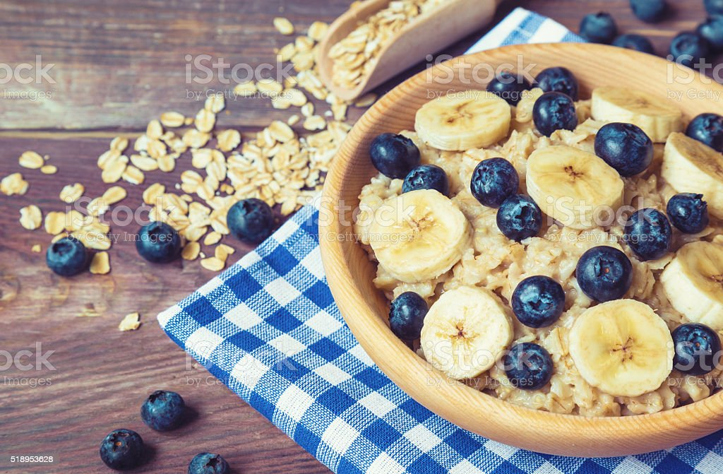 Oatmeal with blueberries and banana in wooden bowl stock photo