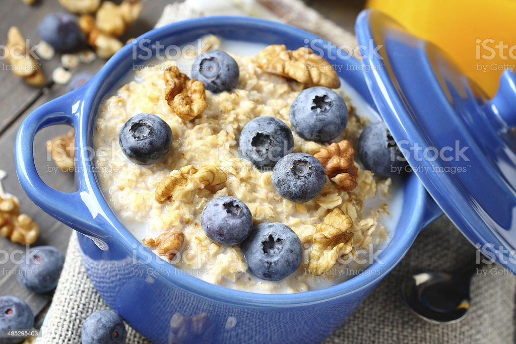 Oatmeal with fresh blueberries over a rustic wooden background stock photo