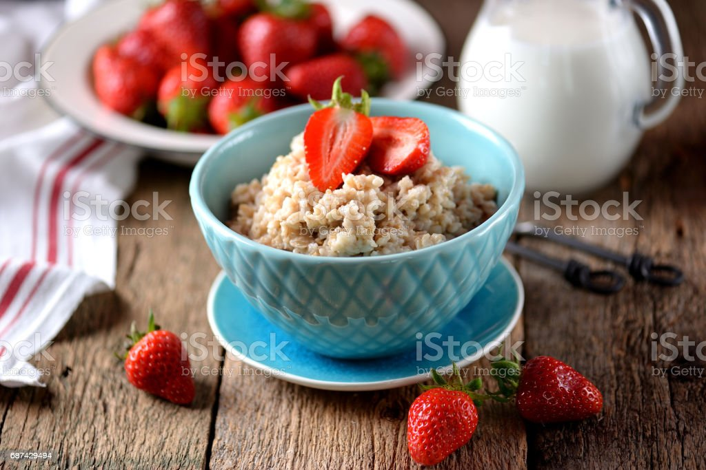 Oatmeal with fresh strawberries and milk on an old wooden background. Healthy breakfast. Healthy food. stock photo
