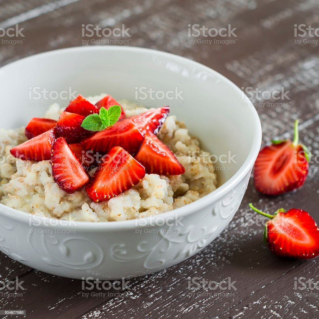 Oatmeal with honey and strawberries in a white bowl stock photo