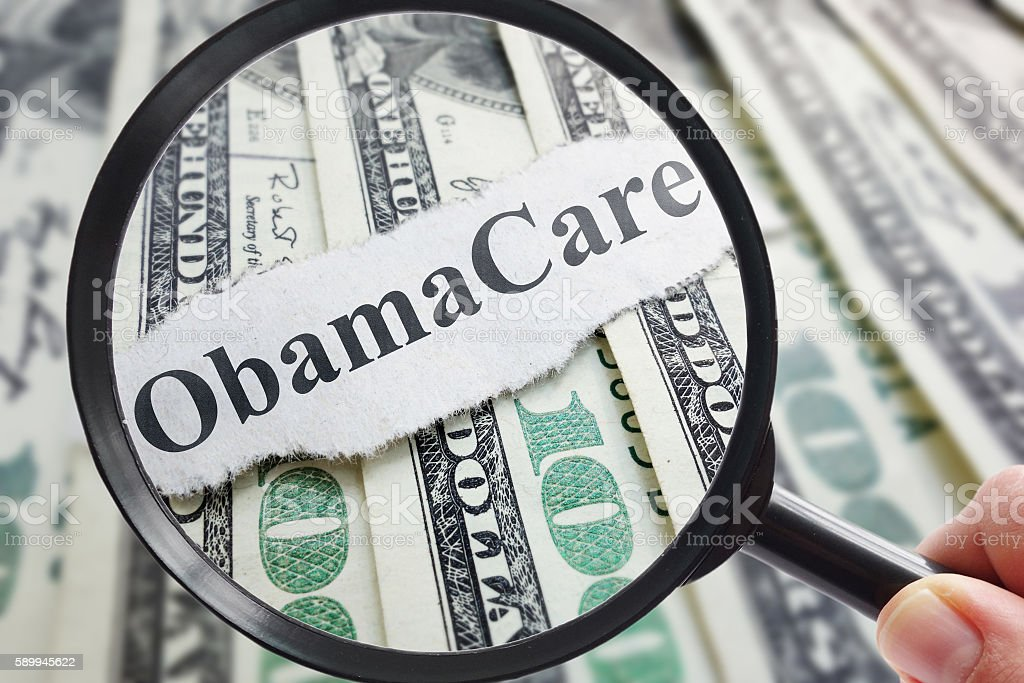Obamacare and magnifying glass stock photo