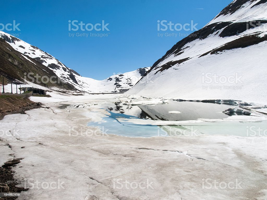 Oberalp pass, Artificial lake ice stock photo