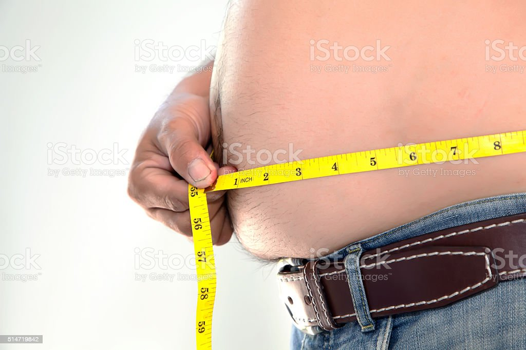 Obese person measuring his belly. stock photo