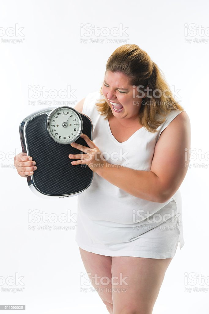 obese woman looking angry at scale stock photo
